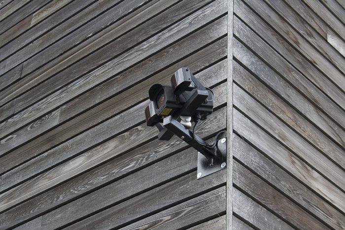 CCTV camera on wooden panels on the side of a building