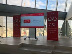 Stage set up for CSL conference, with two pop-up stands and a large tv with CSL branding