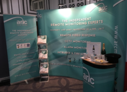 Arc Monitoring's exhibition stand, including a backdrop, pop-up stand, leaflet stand and carry case with Arc merchandise and competition prize