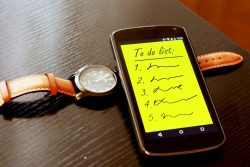 To do list on mobile screen next to an orange strapped watch